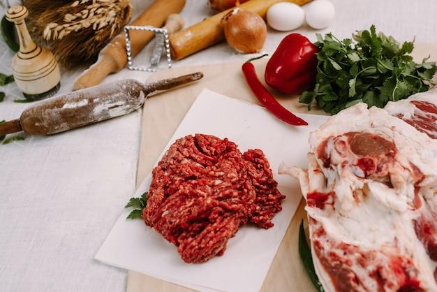 Świeże czerwone mięso mielone na tle mięsa i przypraw.