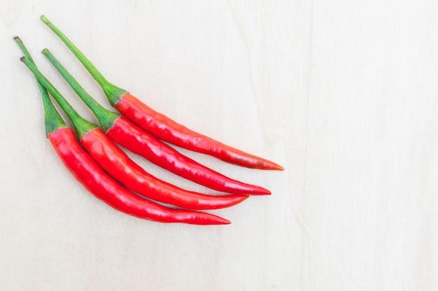 Świeże czerwone ostre papryczki chili z pikantnym na drewnianym stole z miejsca na kopię