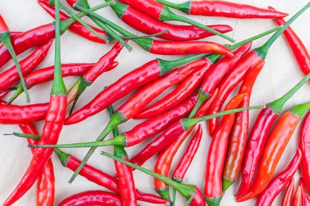 Świeże czerwone ostre papryczki chili z pikantnym na tle drewniany stół
