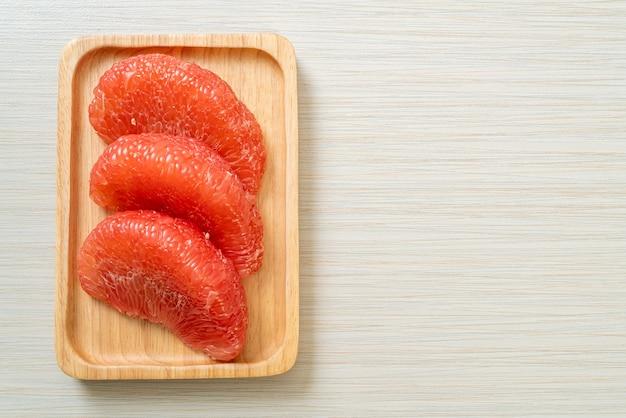 Świeże czerwone owoce pomelo lub grejpfrut na talerzu