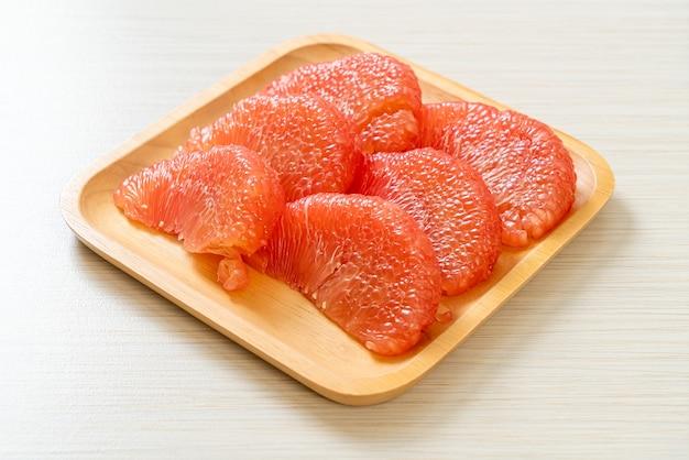 Świeże czerwone owoce pomelo lub grejpfruty na talerzu