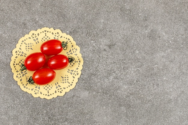 Świeże czerwone pomidory czereśniowe na szaro.