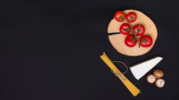 Świeże czerwone pomidory; ser; grzyb i pęczek makaronu spaghetti na blacie kuchennym