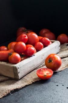 Świeże czerwone pomidory w drewnianym pudełku na czarnym tle.
