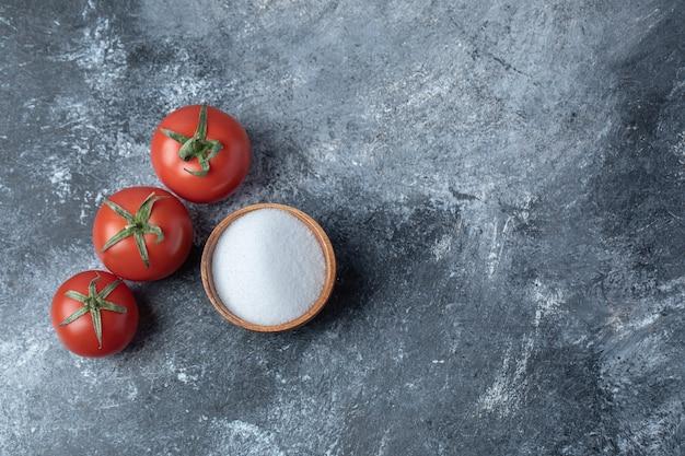 Świeże czerwone pomidory z drewnianą miską pełną soli.