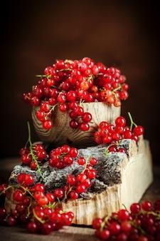 Świeże czerwone porzeczki na ciemnym rustykalnym drewnianym stole