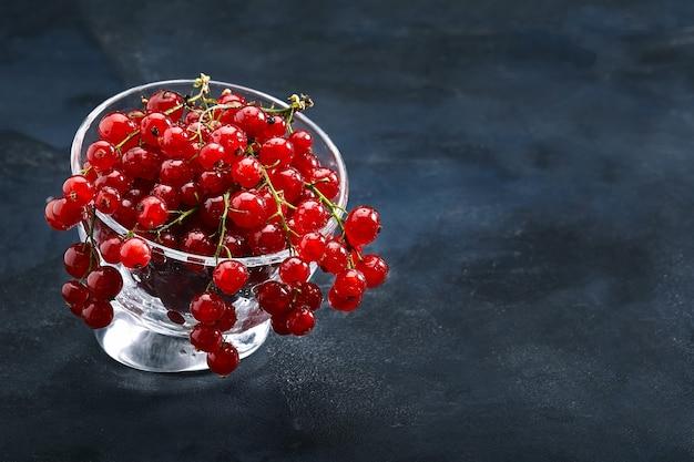 Świeże czerwone porzeczki na ciemnym tle zbliżeniu. koncepcja świeże jagody, dostawa artykułów spożywczych. zdjęcie dla kolologa ze sklepu spożywczego. skopiuj miejsce.