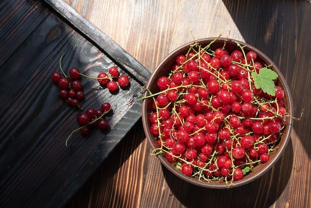 Świeże czerwone porzeczki w misce na drewnianym stole i jagody, z bliska.