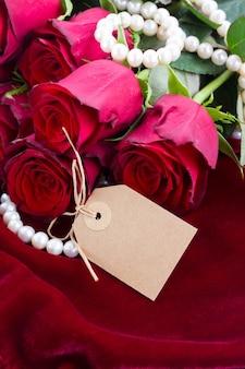 Świeże czerwone róże na tle szkarłatnego aksamitu z klejnotami i pusty tag