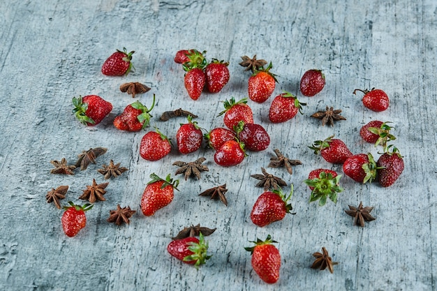 Świeże czerwone truskawki i goździki na powierzchni marmuru