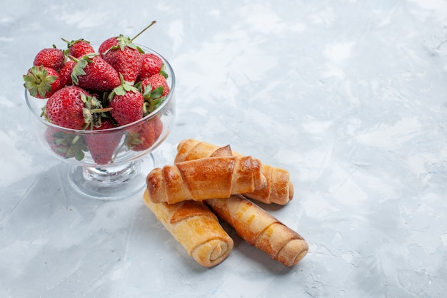 Świeże czerwone truskawki łagodne letnie jagody wewnątrz szklanego talerza ze słodkimi bransoletkami na lekkim biurku