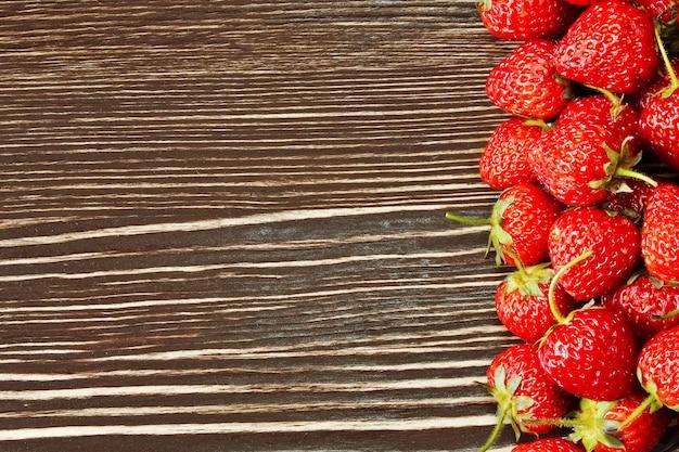 Świeże czerwone truskawki na brązowym tle drewnianych