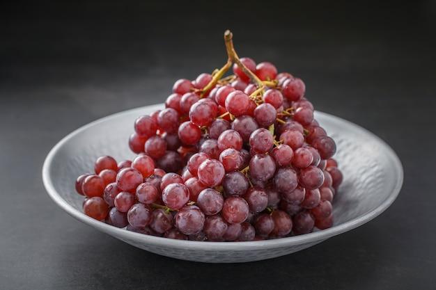 Świeże, czerwone winogrona w ładnym metalowym talerzu