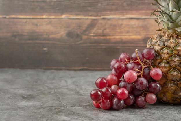 Świeże czerwone winogrona z dojrzałym ananasem na marmurowej powierzchni.