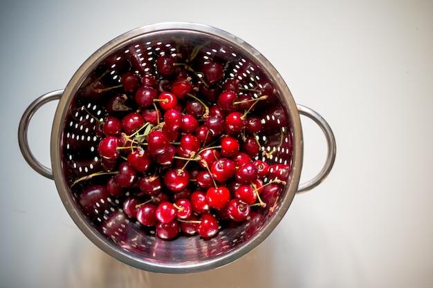 Świeże czerwone wiśnie myją w durszlaku.
