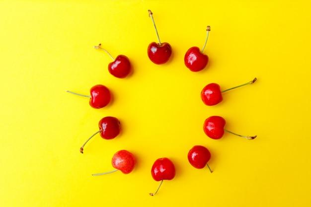Świeże czerwone wiśnie na żółtym tle, reklama, plakat.
