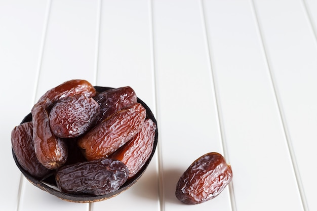 Świeże daty medjool w drewnianej misce kokosowej.