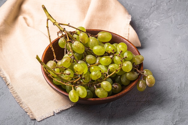 Świeże, dojrzałe białe jagody winogronowe w drewnianej misce na lnianym obrusie