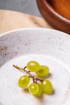 Świeże, dojrzałe białe jagody winogronowe w drewnianej misce z płytą na lniany obrus, beton, kąt widzenia makro