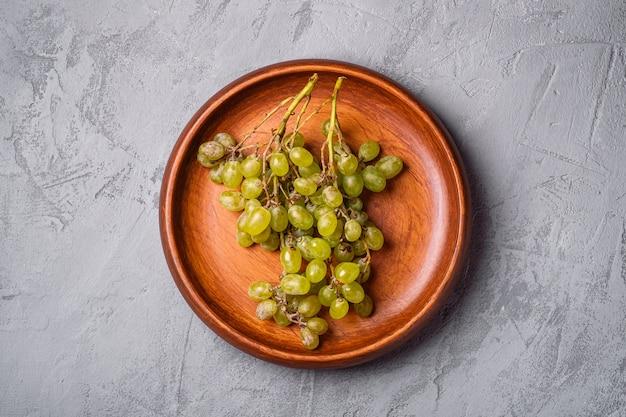 Świeże, dojrzałe białe jagody winogronowe w drewnianej tablicy na kamieniu