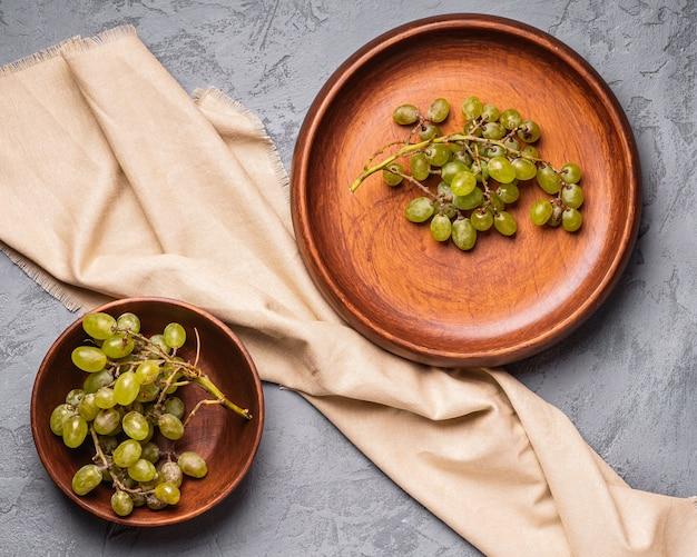 Świeże, dojrzałe białe jagody winogronowe w drewnianym talerzu i miski na lnianym obrusie