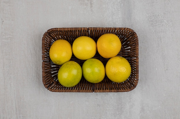 Świeże dojrzałe cytryny na drewnianym koszu.