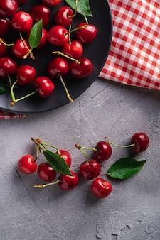 Świeże dojrzałe czereśniowe owoc z zielonymi liśćmi na czarnym talerzu z czerwonym naczynie ręcznikiem, lato witaminy jagody na popielatym kamiennym tle, odgórny widok