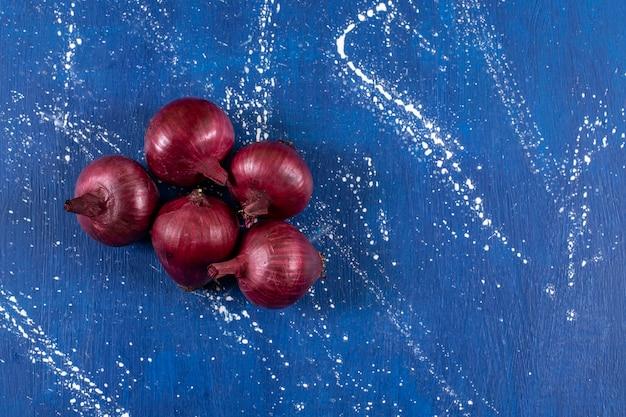Świeże dojrzałe czerwone cebule umieszczone na marmurowej powierzchni.
