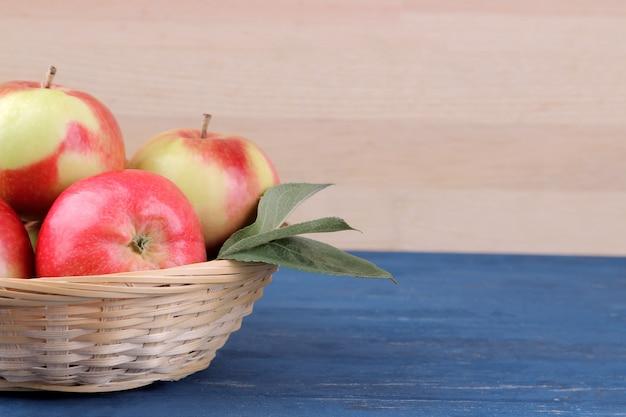 Świeże dojrzałe czerwone jabłka z liśćmi w koszu na niebieskim drewnianym stole i na tle naturalnego drewna z miejscem na napis