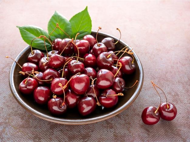 Świeże, dojrzałe czerwone wiśnie na płycie gliny na ciemnym niebieskim tle. pojęcie zdrowego odżywiania. jedzenie wegetariańskie.