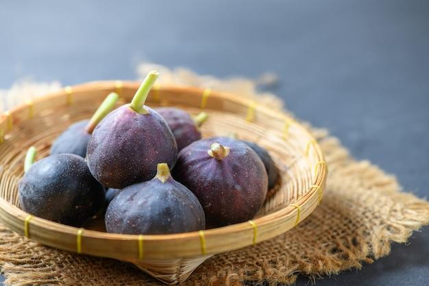 Świeże dojrzałe figi w bambusowym koszu na ciemnym stole. zdrowe owoce figi śródziemnomorskiej.