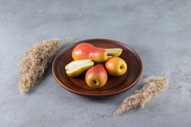 Świeże dojrzałe gruszki na brązowym talerzu z kłosami pszennymi ułożonymi na kamiennej powierzchni.