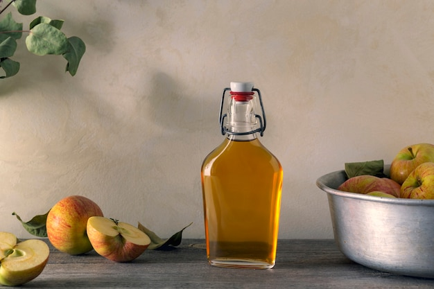 Świeże, dojrzałe jabłka i ocet jabłkowy. cydr jabłkowy w szklanej butelce i świeże jabłka. jasne tło.