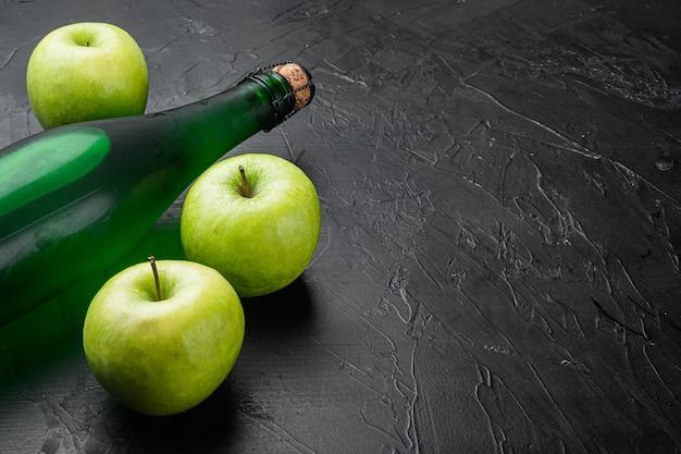 Świeże dojrzałe jabłka i zestaw octu jabłkowego, na czarnym ciemnym tle kamiennego stołu, z miejscem na kopię tekstu