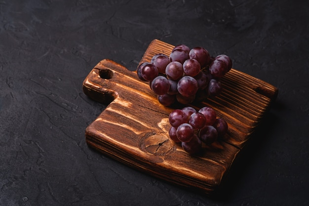 Świeże, dojrzałe jagody winogron na brązowej drewnianej desce do krojenia na ciemnym tle kamienia, kąt widzenia