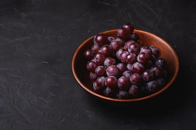 Świeże, dojrzałe jagody winogron w brązowe drewniane miski na ciemnym tle kamienia, kąt widzenia