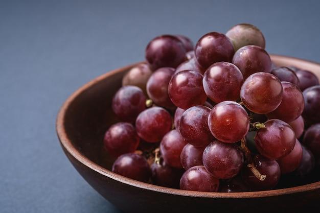 Świeże, dojrzałe jagody winogronowe w brązowej drewnianej misce na niebiesko-szarym minimalnym tle, makro kąt widzenia