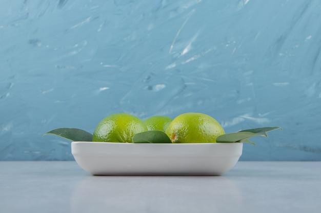 Świeże, dojrzałe limonki na białym talerzu.