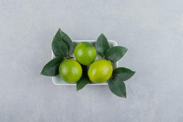 Świeże dojrzałe limonki na białym talerzu