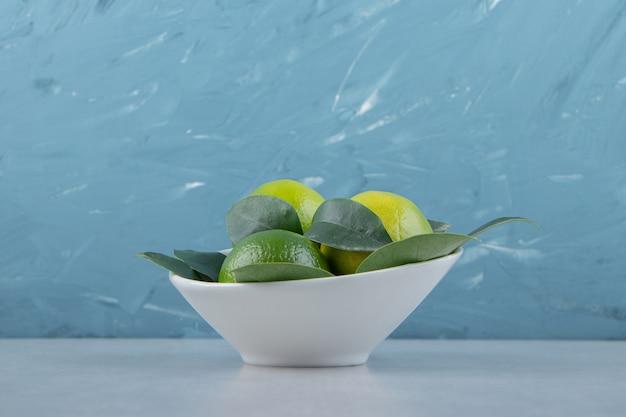 Świeże dojrzałe limonki w białej misce