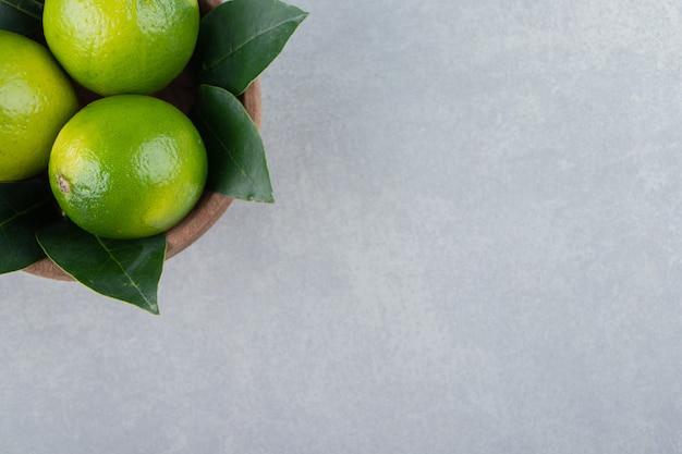 Świeże dojrzałe limonki w drewnianej misce.