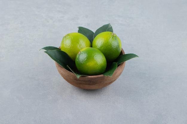 Świeże dojrzałe limonki w drewnianej misce