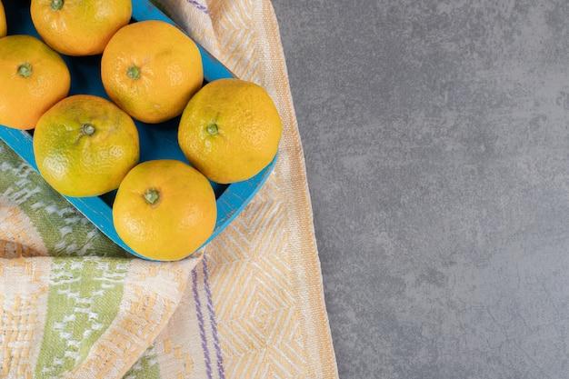 Świeże dojrzałe mandarynki na niebieskim talerzu. zdjęcie wysokiej jakości