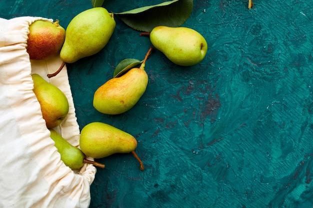 Świeże dojrzałe owoce gruszki w sznurkowej eko-torbie na zakupy wielokrotnego użytku na zielonym tle koncepcja spożywcza