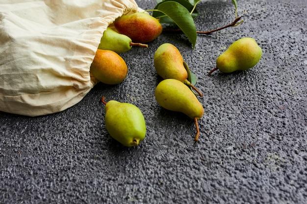 Świeże dojrzałe owoce, gruszki w sznurku wielokrotnego użytku eko torba na zakupy na ciemnym tle, koncepcja spożywcza, płaski świecki, ekologiczny, jesienne zbiory. skopiuj miejsce.