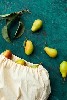 Świeże dojrzałe owoce gruszki w sznurku wielokrotnego użytku eko torba na zakupy na zielonym tle, koncepcja spożywcza, płaski świecki, ekologiczny, jesienne zbiory. skopiuj miejsce.