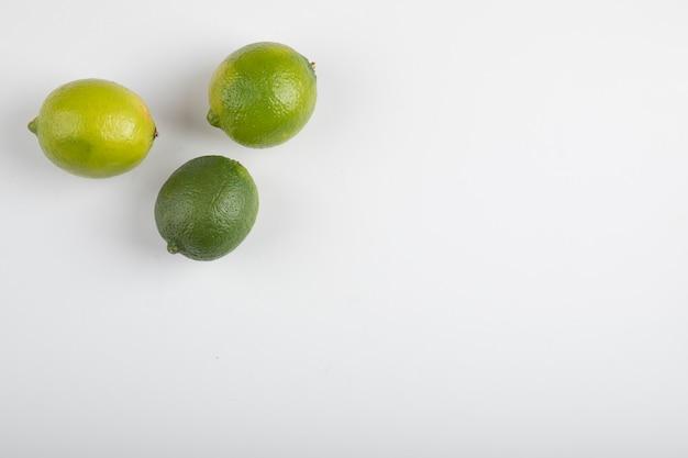 Świeże, dojrzałe owoce limonki na białym tle.