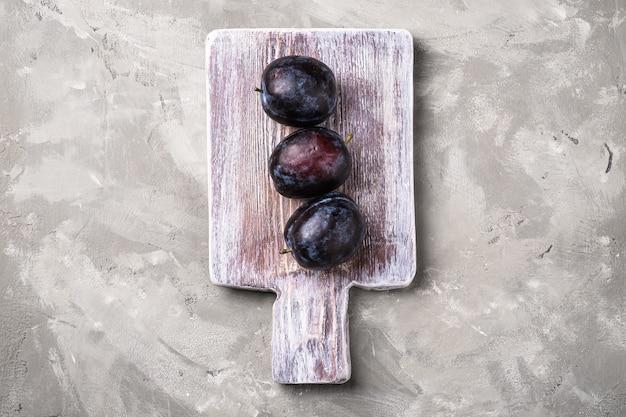 Świeże, dojrzałe owoce śliwki na drewnianej desce do krojenia