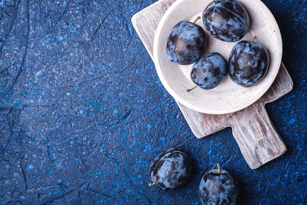 Świeże dojrzałe owoce śliwki w białej drewnianej misce i starej desce do krojenia na niebieskim tle streszczenie, widok z góry kopia przestrzeń