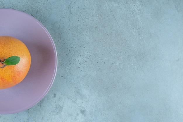 Świeże dojrzałe pomarańcze na talerzu, na marmurowym tle.